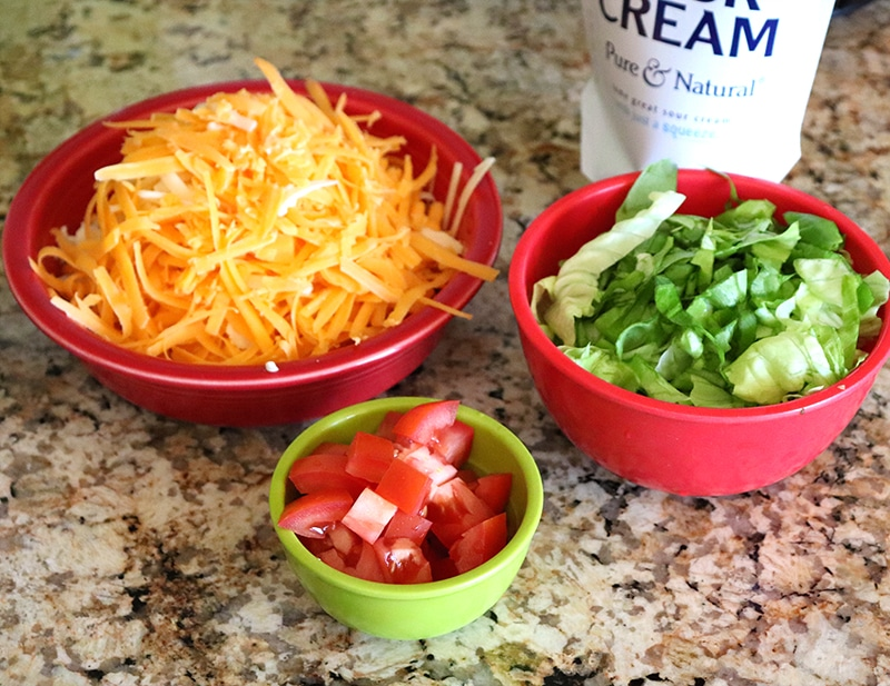 Toppings for beef fajitas with shredded cheese, lettuce, diced tomatoes, and sour crem