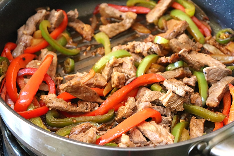 A pan of beef fajitas with roasted bell peppers.