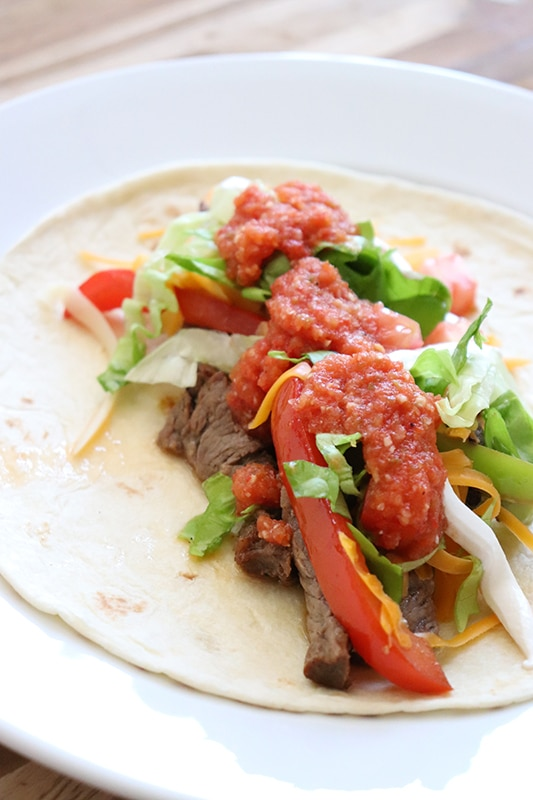 Close up of beef fajitas on a round white plate