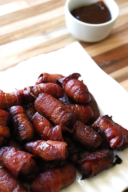 Bacon wrapped lil smokies on a white place with a side of sugar free bbq sauce