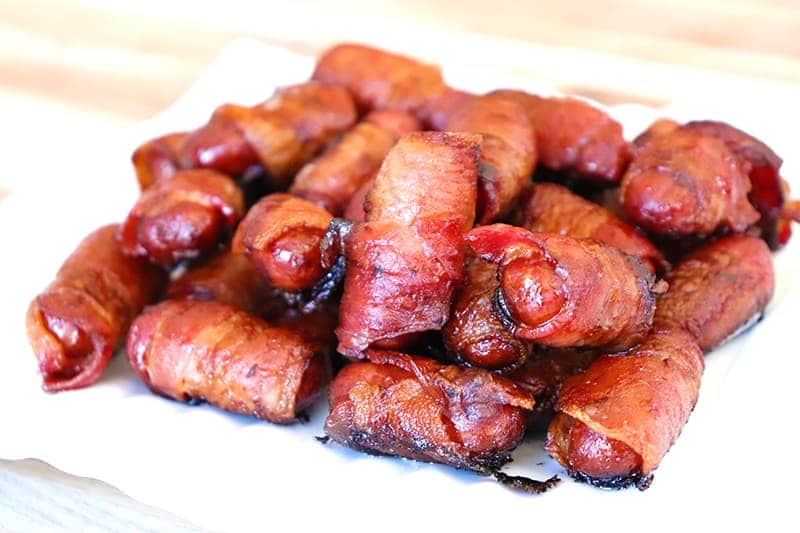 Lil smokies wrapped in bacon, based with sugar free bbq sauce on top of a white place with a blurred background