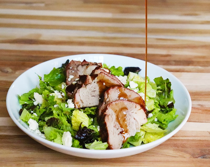 drizzling balsamic vinegar and olive oil over a pork loin salad