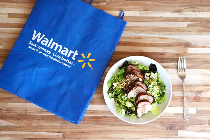 a pork loin salad in a bowl, with a fork, next to a walmart reusable grocery bag