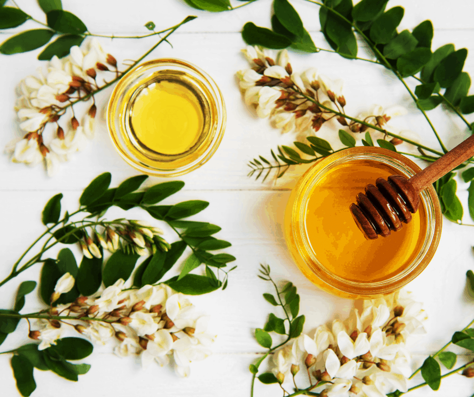 white flowers and ivy leaves along side a jar of honey and oil
